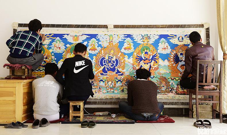 热贡画院三层的培训室很空旷,画师们席地而坐,画纸靠在墙上,身边不时会有老师来指点。