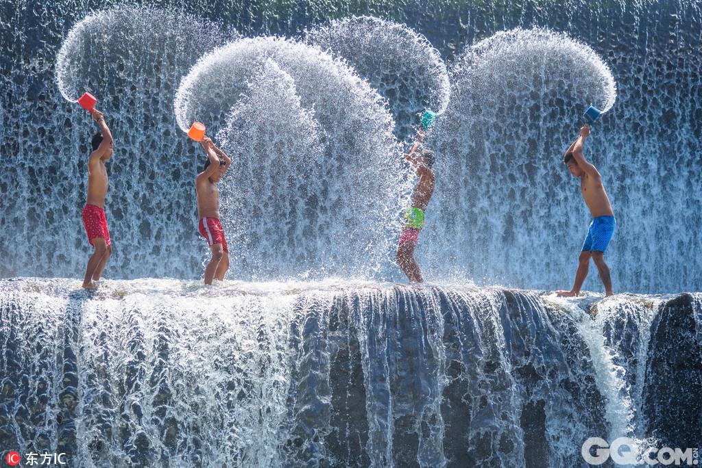 摄影师拍巴厘岛少年瀑布上戏水