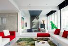 """客厅区域非常开阔,所有落地窗都改成了无框架式,最适宜观赏窗外的景色。左侧正面墙上的综合材料艺术作品来自林天苗,侧面墙上彩虹般的画作是刘韡的""""三明 治""""系列,最右侧的几何立体装置也是他的作品,以上艺术品均来自长征空间。正中央大卫脸形象的马赛克墙面由Bisazza出品,它连接着天花板上的射灯灯 带,渲染出舞台布景的效果。近处沙发区,鹦鹉图案地毯来自毯言织造,白色茶几上的两个盘子是Robert Mapplethorpe为Ligne Blanche品牌设计的,来自10 Corso Como。"""