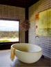 沐浴时最能净化人身心的,无外乎窗外沁人心脾的风景。主卧位于房屋的另一侧,浴缸来自Boyd Design。