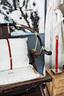 """这张座椅是沈伟10多年前于北京传统家具店寻宝所获,他喜欢这张宋朝风格座椅的干净简单线条感,木质厚实,还可以折叠。抱枕则是他自己设计制作,以深红色皮条加上金属扣缝制于抱枕上,和座椅的金属相应衬托,也可窥见沈伟对细节的讲究。沈伟钟情于传统但不醉心于旧物,也无法认同冰冷的现代设计,""""破旧立新是我很喜欢的。"""""""