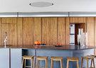 胡桃木面板后藏着各种厨房电器、家什,避免了凌乱感,并从视觉上带来可靠的温馨。餐厨空间里大面积使用了胡桃木贴面,操作台上方那个被照亮的圆盘是一个排风扇,这样的设计可以避免因下垂的设计而破坏生活区视觉上的整体性。
