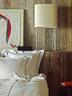 从加拿大旧谷仓中搜集来的老橡木已经年过百岁,简单的重新磨光和修正后,就散发出浓浓的时光味道。另一间卧室中,床头灯由Paolo Rizzato设计,出品自Arteluce。