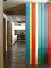 越过公寓入口处彩色喷漆的金属立面,可以看见远处的Boffi厨房。