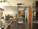 在一些精心选定的特殊位置上,安放些许彩色家具和饰品,笼统黯淡的木色格局由此被轻松打破。双面壁炉隔开了餐厅与客厅,一块喷涂了彩色漆的金属立面覆盖在入口处的衣橱上,成为了木色空间中的亮点,这同样是Thierry Lemaire的设计。