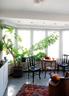 """厨房中充满了绿意浓浓的自然气息,一张上海民国时期的洋式圆桌为柚木材质,两把椅子是红木的。近处的木桶椅为椴木材质,源于清代的山东。这几件木家具都来自""""林松轩""""。"""