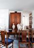 """客厅中能看到安装木地板失败后换上的浅灰色大理石地面,核桃木的餐桌和座椅是仿古制品,桌上的白色瓷瓶也是宋代样式。""""非常漂亮,也买了很多年,但不敢说是不是真的宋代瓷器。""""后面的榉木立柜则是清末民初的古董家具,以上木家具都来自古董以及仿古家具经营商宋林松的""""林松轩""""。远处门框上的猫形贴画有如一只淘气爬高的猫咪,给这个优雅、规矩的家带来一丝调皮气息。"""