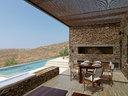 户外用餐区,一旁是阳光房和朝向大海的泳池。