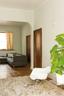 原有的玻璃门一直通向起居室。灰褐色地毯来自宜家家居,Eames白色摇椅和绿植增添了一份清新。