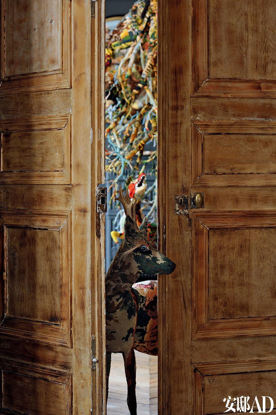 用挂毡拼接制作的小鹿从古老的公寓大门探出头来,仿佛要将我们带入一片神奇之地。