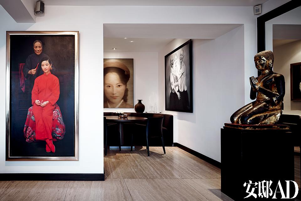 """从1990年代起,主人在画廊好友的引领下开始收藏画作,如今其收藏已经相当成规模。左侧的大幅写实油画作品来自王沂东的""""约会春天""""(Springtime)系列,它的右侧是早餐餐厅,餐桌来自意大利,后方是祈志龙的作品《消费形象02号》,右侧墙上的画作《秃头与时尚》来自刘飞,斑驳的古董跪坐铜佛像与家中的另一尊佛像是一对。"""