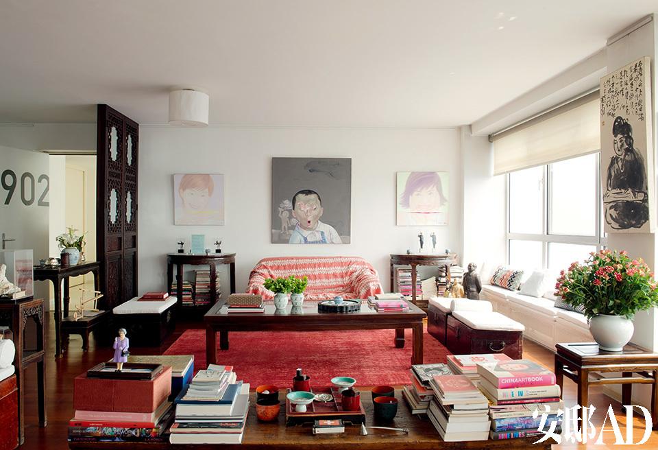 满屋的画作见证了主人与一众中国当代艺术家们的亲密情谊。靠墙的两座半圆形木质边几上分别摆着来自施勇和瑞士雕塑家Laurenz Metzler的雕塑作品,边几上方的两幅女性肖像画由Yang Man创作,以上都来自ShanghART画廊。墙面正中央的油画由尹堃创作于2000年,地毯来自毯言织造。