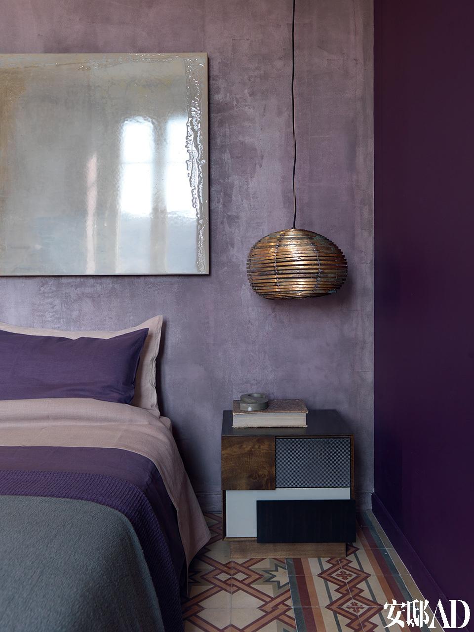 卧室被漆成极富戏剧性的紫色调,带有金属元素的装饰物和艺术品为整个房间增色不少。卧室的墙面被漆成了极富戏剧性的紫色,却仍与地砖上的彩色图案相衬。床上的被单、床头墙面上精致的淡绿色艺术品,都与床头柜的色调巧妙呼应。靠枕、床单、床罩的选择,更是助长了卧室里这种戏剧化的配色效果。