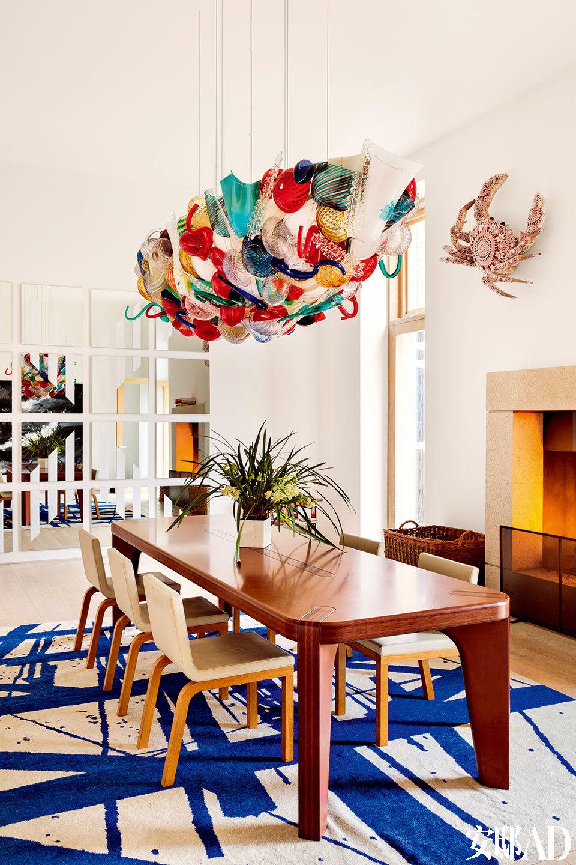 餐厅中,壁炉上方是葡萄牙艺术家Joana Vasconleos的陶瓷蟹雕塑,周身覆满编织的网状图案。餐桌来自Marc Newson,带蓝色不规则线条的地毯由Tony Bevan设计,ChristopherFarr生产。餐桌上方的船形吊灯出自Campana兄弟之手,由Venini公司使用穆拉诺玻璃制造。