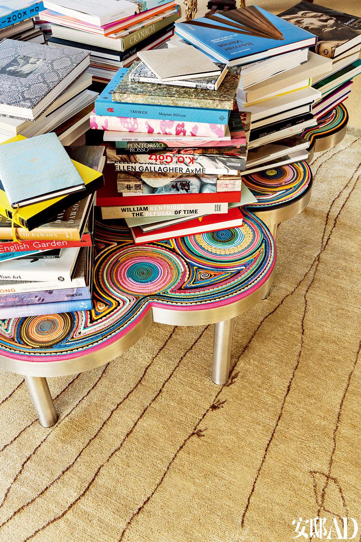 """以寿司为灵感的设计化作色彩斑斓的长凳,再堆上成摞的书籍,仿佛一件雕塑再创作。客厅的细节,Campana兄弟设计的""""春卷长凳""""(Harumaki Bench)完成于2007年,属于他们的""""寿司系列"""",不锈钢底座搭配木质座面,表面覆盖着用毛毡、橡胶、EVA材料、布料和防滑垫手工制作的彩色""""寿司卷""""。"""