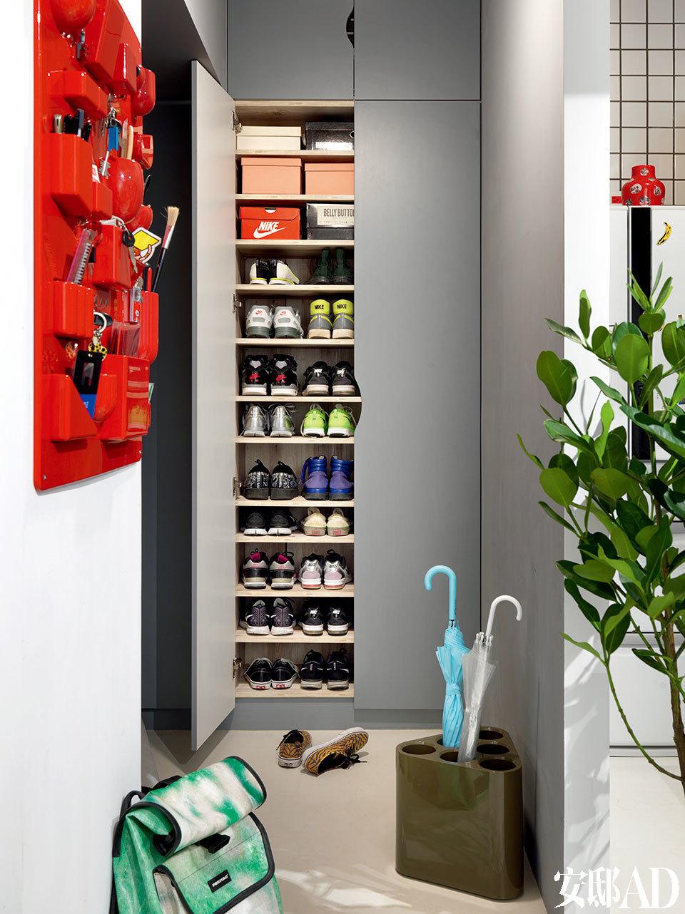 """""""想一千次,不如切切实实做一次!""""85后设计师Pili秉持着如此信念和对自己生长之地的挚情,坚守在自己的设计路上。对他而言,设计从不是炫耀之事,而是诚实之情!进门的玄关被良好利用,做成了""""顶天立地""""式的鞋柜。墨绿色伞筒来自Magis,右上角的红色小花瓶是Pili的""""漆瓷""""系列作品(www.utp.tw)。"""