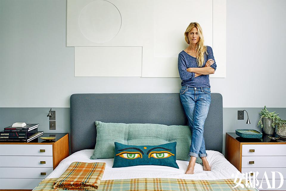 卧室床头的设计选用了Kvadrat出品的灰绿色羊毛面料,眼睛图案靠枕和毯子出自室内设计师Florence Lopez的朋友、现居巴黎的瑞典设计师Gabrielle Soyer创办的Lindell &Co品牌。床的两边,Florence舍弃了常见的床头柜,选择了两个George Nelson于20世纪50年代设计的小抽屉柜,大大增加了储物空间。她还用明亮的颜色设计了床头墙面的错视艺术,致敬英国抽象大师Ben Nicholson。 主人: Natacha Sénéchal,是一位 住在巴黎的模特,她也是Helmut Newton、Annie Leibovitz、JeanFran?ois Jonvelle等著名摄影师镜头下的女神,她曾出现在意大利版ELLE 、拉美版Bazaar 、法版Madame Figaro 等杂志的封面。