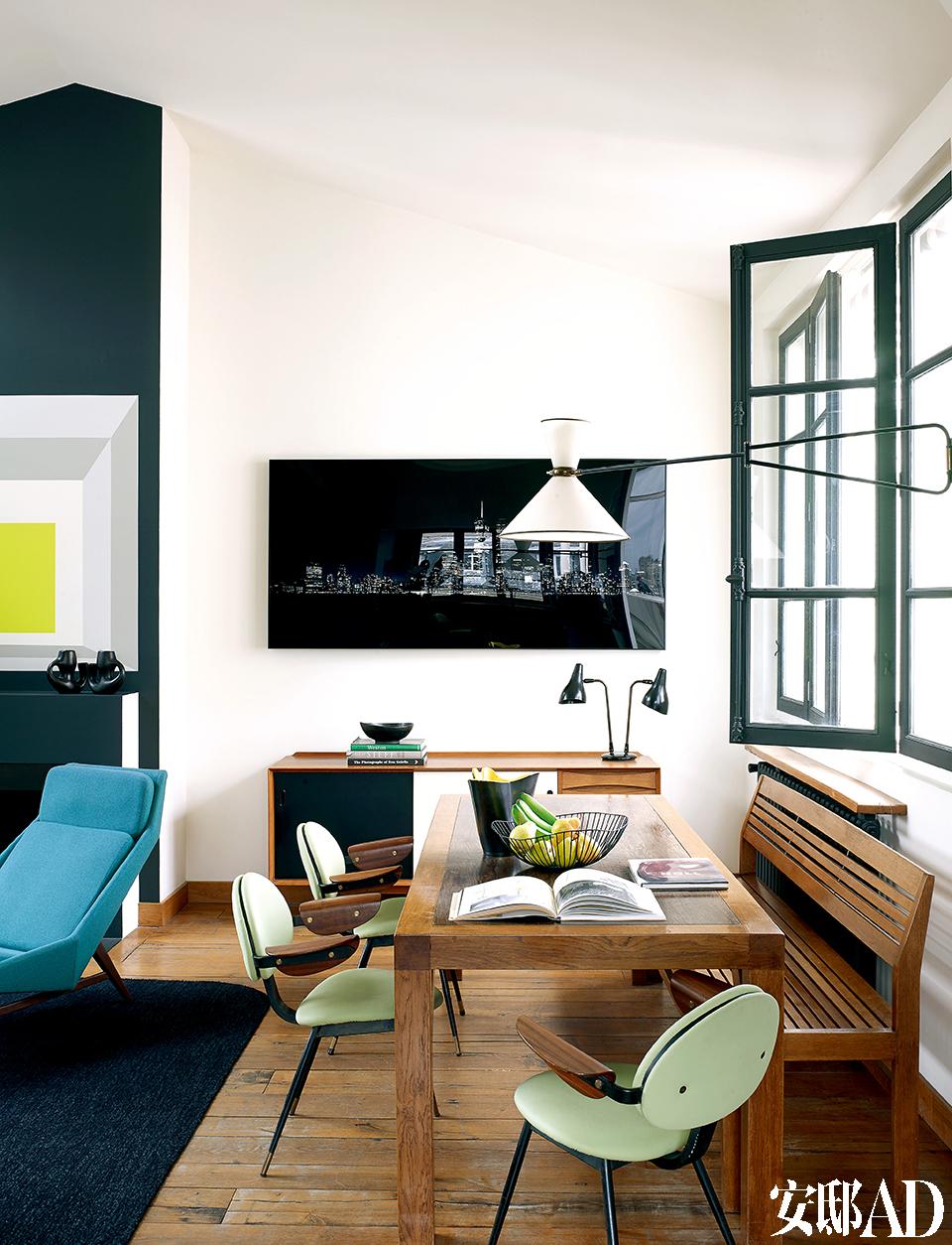 20世纪五六十年代的古董家具和空间里明亮的色彩完美互补,令家里色彩缤纷,又 不失稳重。客厅壁炉一侧便是餐厅,Florence Lopez设计了橡木餐桌和长凳,绿色扶手椅由Carlo Mollino出品,壁灯是20世纪50年代的作品,出自法国建筑师兼设计师Pierre Guariche之手。