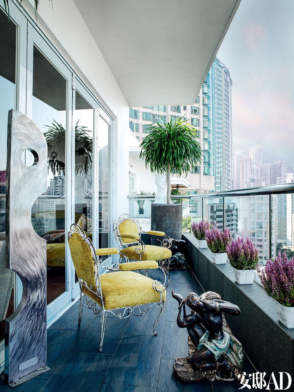 户外阳台能俯瞰整个香港市区的美景。两张法式扶手椅来自上世纪20年代,在它们旁边是一件上世纪70年代的金属雕塑。