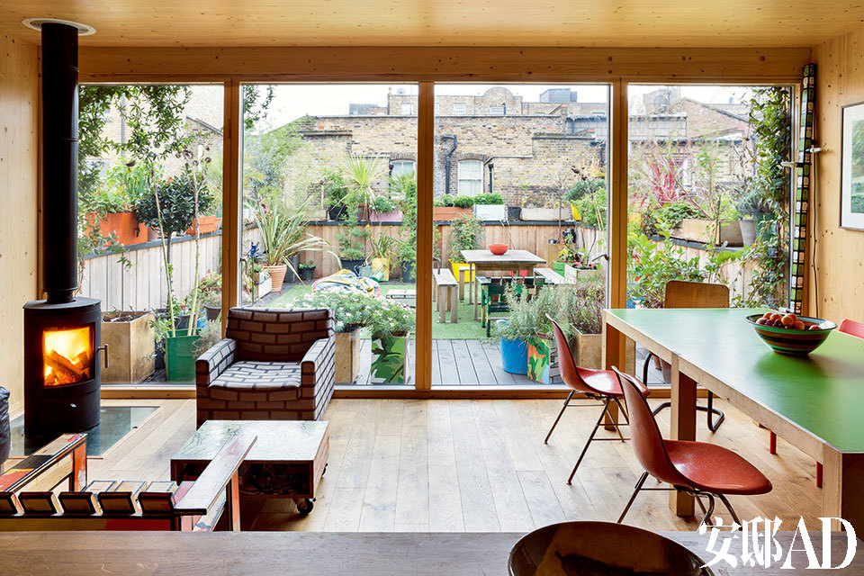"""餐厨空间以落地玻璃与露台相连,露台同样延续了室内的多彩风格, 并种植有许多芳香植物。 在伦敦难得的好天气里,主人可不会错过在这里晒太阳。餐厨空间直接连通户外露台,左边近景处的木制扶手椅是""""Dirty Chair,2013""""的原型,它跟中间的茶几一样都是Richard Woods的设计。"""