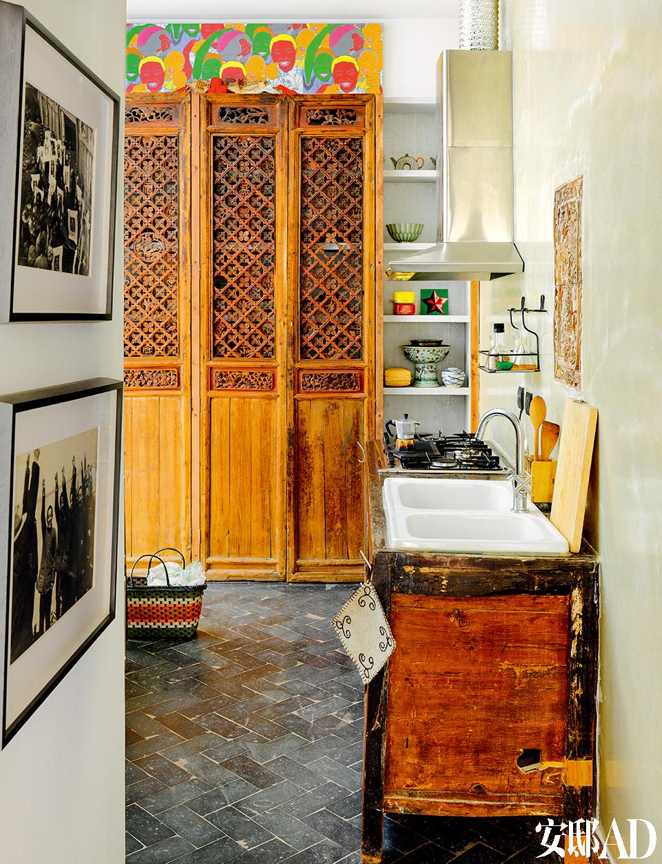 厨房在一层,虽然不大,但精致而带有艺术气息。橱柜是从谷物橱柜改造而来的,是从北京的古玩店里淘的。雕花柜门也是从古玩市 场里买的。储物柜上的彩色画作是2008年奥运会期间购买的,以前挂在旧公寓的客厅,现在挪到了厨房。