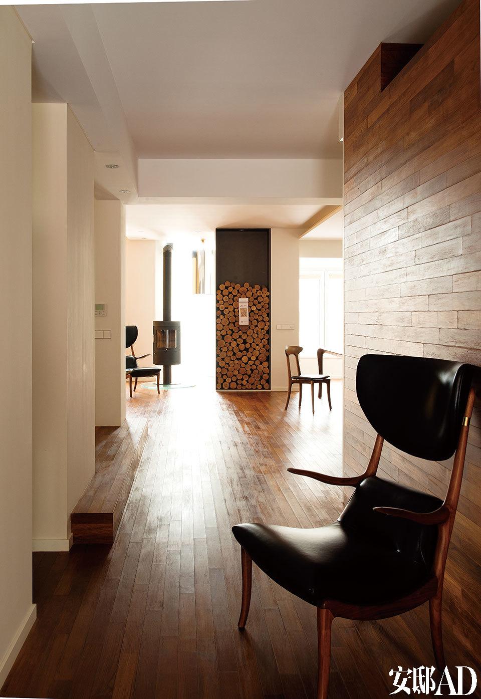 """家中的扶手椅形态纤巧曼妙且非常轻便,可以随意挪动到任何需要它们的地方。近处这把椅子的背后是厨房,地板的木料同样延伸到了这面墙上,让整个空间显得非常统一而现代感十足。远处的HWAM壁炉造型简单而实用性强,它现在已经是陈俊华的最爱。""""每当屋外下起雪,父亲就拾了柴禾燃起壁炉,一家人温暖地坐在沙发上看着红红的火焰,这种感觉总会勾起我的童年回忆。"""""""