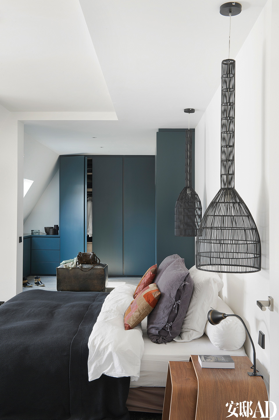 阁楼上的主卧室,床两侧的吊灯来自Ayilluminate,床品是Ralph Lauren品牌,床头柜来自Flamingo。与墙面吻合的衣橱为量身定制,喷涂成了亚光的深蓝色。