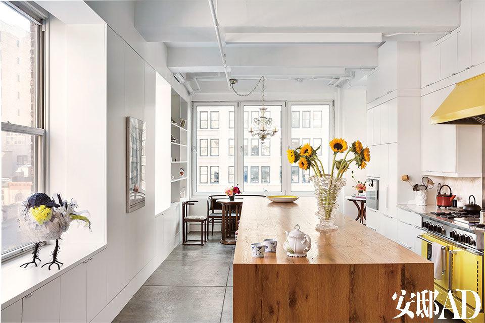 """厨房和餐厅中,一张原木的岛台兼餐桌上摆着韩枫在2003年设计的玻璃花瓶,明黄色的搪瓷大铁盘与同色系的Blue Star厨电设施完美搭配。窗台上的小鸟""""黛玉""""由铁丝骨架和丝绸材质制成,也是韩枫的设计,2008年它曾在维多利亚与艾尔伯特博物馆展出过。三扇大窗让厨房显得通透明亮,这让近年来爱 上烹饪的韩枫更感到如鱼得水。"""