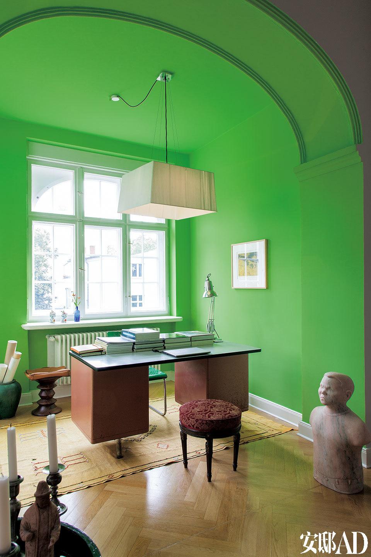 工作区一景,薄钢书桌,制作于1935年,桌子前方是19世纪南德经典坐凳,后方是Eames木座,右侧的雕像来自法国艺术团队Claire Fontaine,地毯购自摩洛哥。