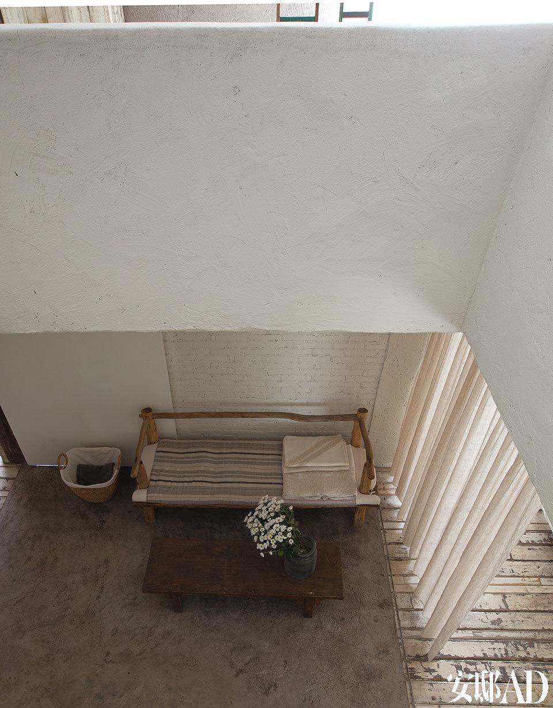 二层俯视一层的一角,木质长椅有着树木的自然弯曲,显得非常粗朴,上面陈列的棉麻材质床单、被套上,可以看到大量手工刺绣的传统花样。茶几由回收的旧木制成,收纳篮由蒲草编织,里面衬着棉布,一旁的苎麻窗帘也由手工纺纱织成,在整个空间中大量用到,质感和透光感都非常好。以上产品皆在无用生活空间内出售或接受定制。