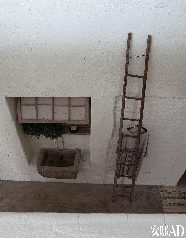 一面高墙上设置了一扇木窗和石质的洗手池,体现出农家院落的味道。一旁的木梯还有晾衣架的妙用。
