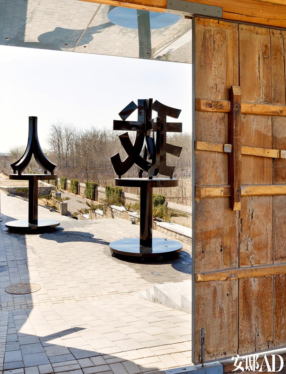 """门口迎客的是黄锐创作的两尊汉字雕塑,转动一下角度可读出里面的"""" 人人为我,我为人人""""。门是从恭王府切来的,他们改造修缮的时候,黄锐把拆掉的旧木板买回来做了自己的大门。门口是他近年来以中国文字为素材创作的雕塑,门口 的是""""人人为我,我为人人""""。"""