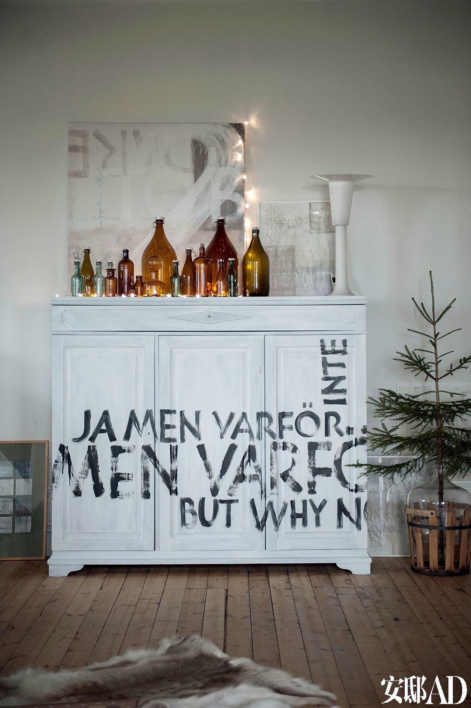 """漂亮的木制品、精致的瓶瓶罐罐,都是最受青睐的圣诞装饰元素。客厅白色柜面上涂写的""""Yes,but why not""""是Ylva最喜爱的一段表达,柜子上还摆放着许多瓶瓶罐罐和美妙精致的蜡烛。"""