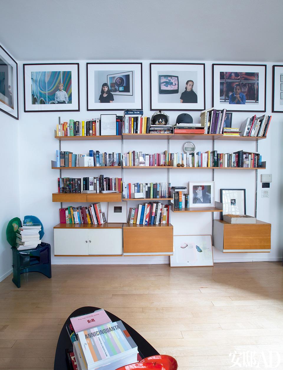 Marconi收藏的艺术画册整齐地摆放在复 古书架上,成为最佳的墙面装饰。墙上的摄影作品出自 Christian Jankowski,左侧的树脂椅是设计师Gaetano Pesce的作品。