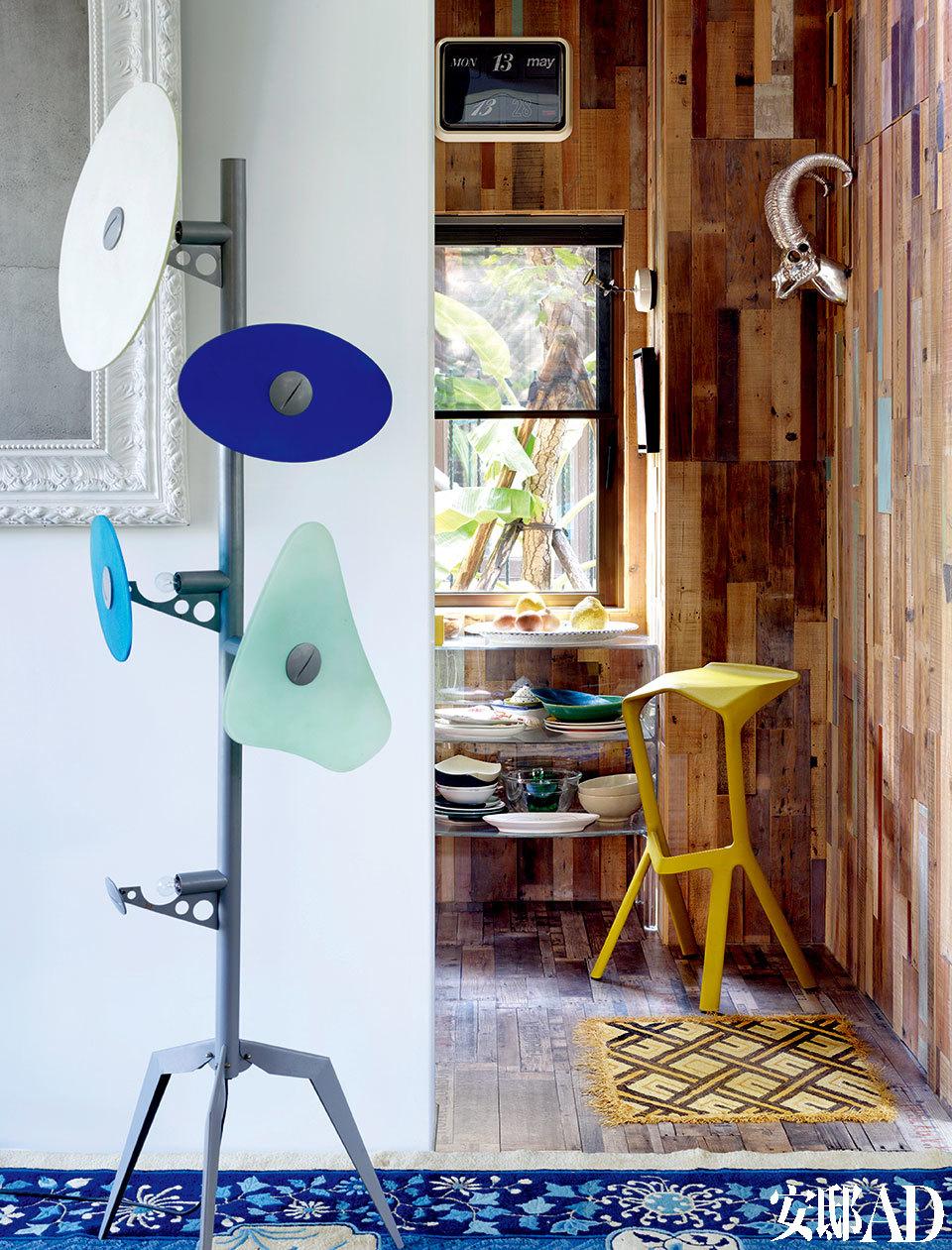 """Orbital Verra""蓝色立灯为上世纪70年代波普艺术后的灯具设计,Foscarini出品。铺上回收木板拼贴墙面,挂着2008年于曼谷旅行买的羊头装置(爱尔兰制造),草绿色高脚椅为设计师Konstantin Grcic的代表作,上有设计师的亲笔签名,Magis出品。"