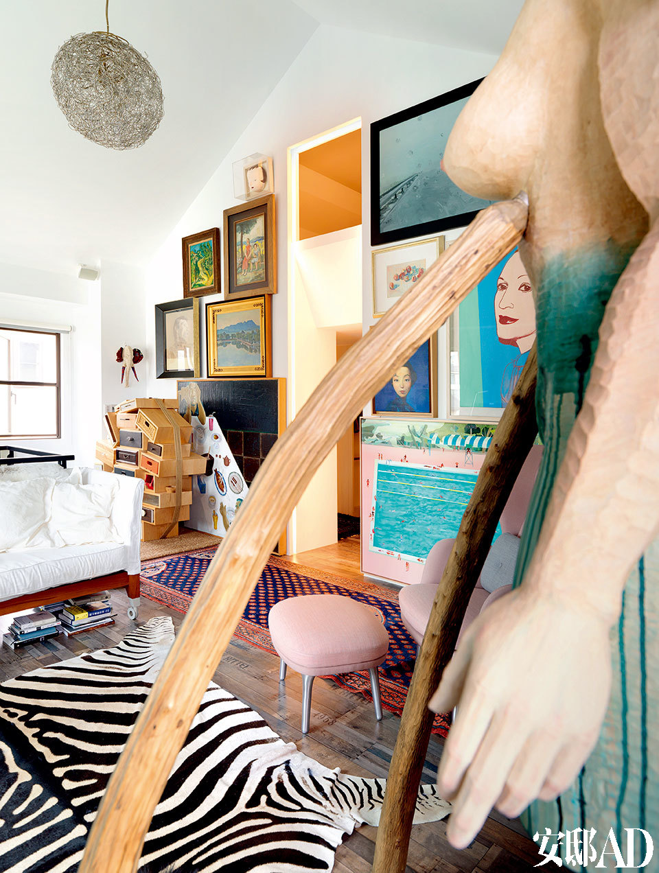 """尽管已经尽力简化,半辈子的艺术收藏还是姚谦生活中的最佳伴侣。顶层工作室,中间小门通往更衣室和阁楼主卧室。吊灯为上世纪90年代最早以鸟巢为灵感设计的灯具。楼梯旁的柜子为设计师Tejo Remy为品牌Droog设计的""""You can't lay down your memory""""抽屉柜。"""