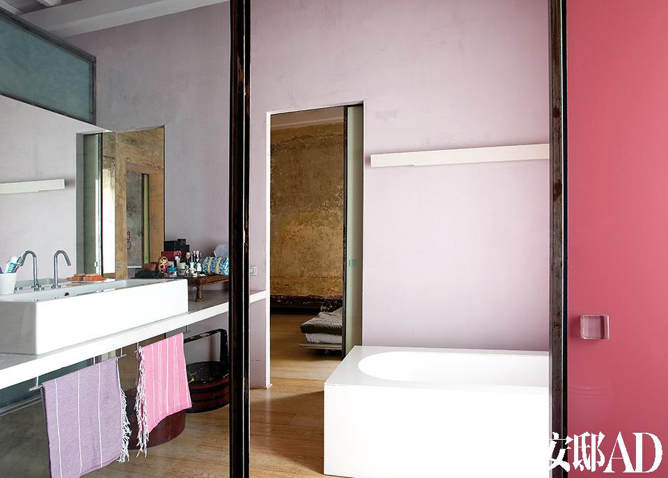 玻璃门反射出的浴室一景。红色、粉色和湖蓝色中和了浴缸硬朗简洁的线条。