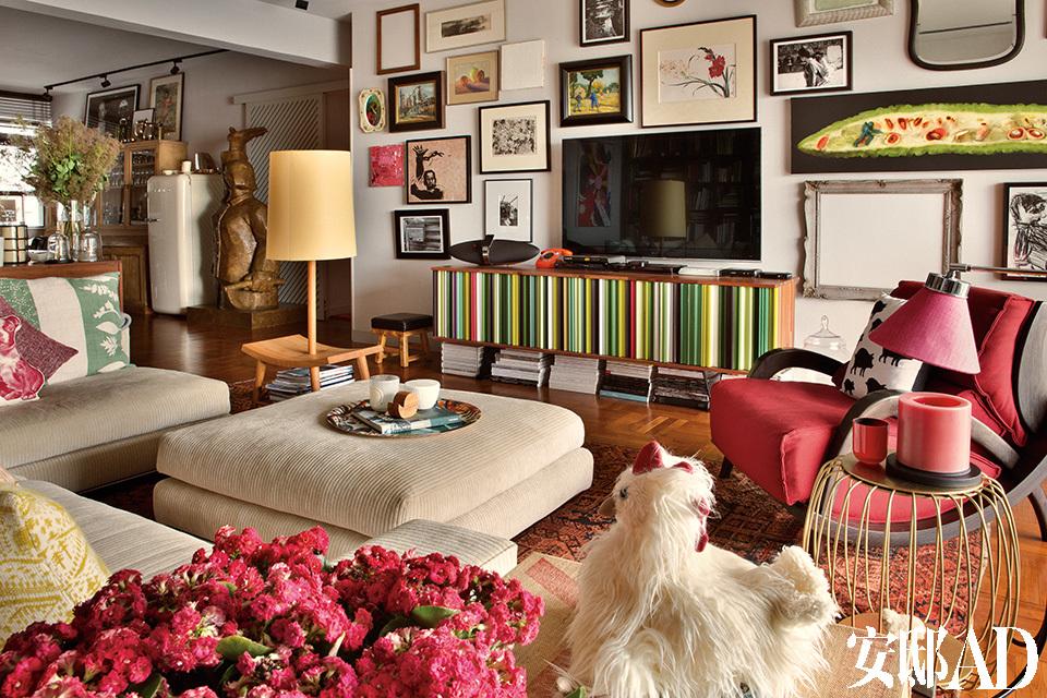 客厅布置得舒服又自在,主人将古董家具、订制家具、动人的艺术品和时髦摆设驾轻就熟地组合在一起。红色Saporiti椅子曾在罗扬杰位于清水湾的家宅中度过了20多个年头,手工电视机柜产自法国,购于香港连卡佛商店。墙壁上挂着精心挑选的绘画和摄影作品,镶嵌在各式各样的框内。