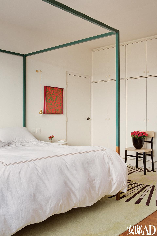 主卧室的摩登版四柱床和床头柜都是在新加坡定制的,表达了女主人黄佩茵对故乡的思念。这个摩登版四柱床以及床头柜是为夫妇定做的,来自新加坡品牌Foundry Collection,墙上挂的艺术作品为艺术家草间弥生1980年代波点画。