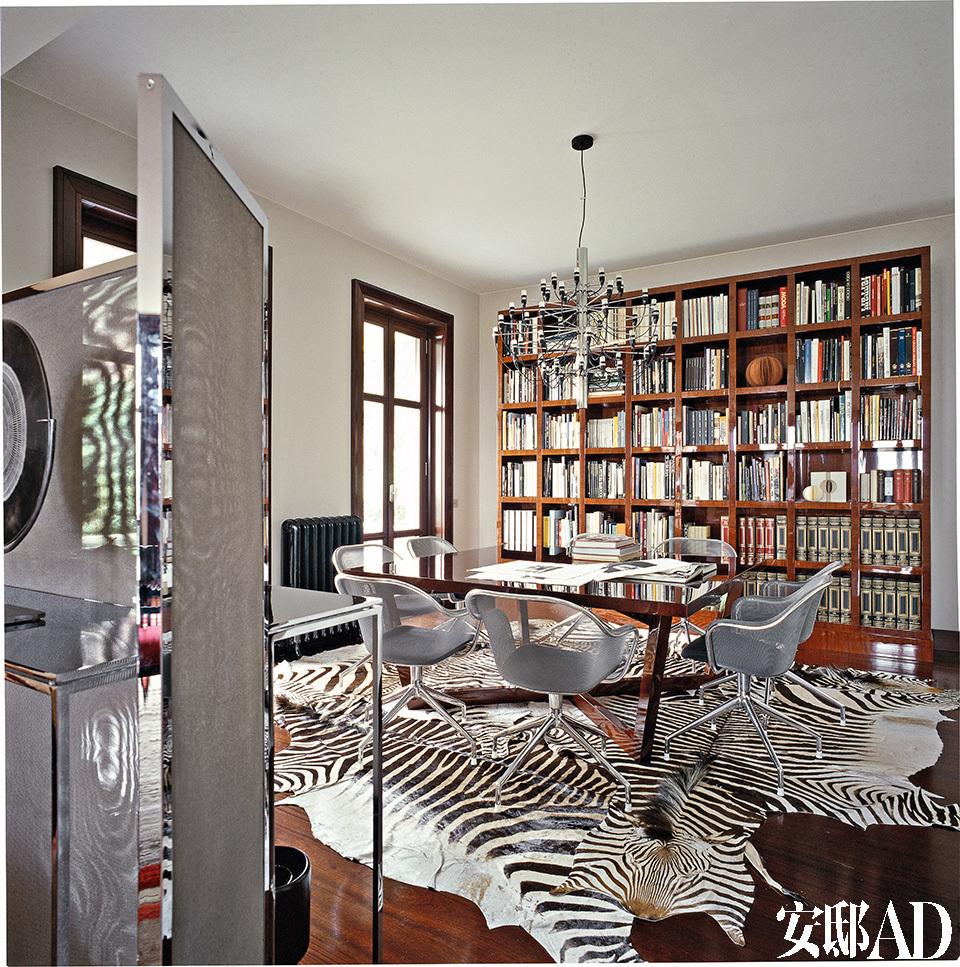 多块斑马皮地毯令餐厅眼前一亮,带金属网椅背的餐椅,与餐厅及客厅之间的金属屏风极为呼应。分隔餐厅与客厅之间的屏风,金属框架内搭配了一种灰色金属细网,为线条明晰的室内风格添加一缕朦胧。Maxalto品牌的餐桌搭配了来自B&B Italia的Iuta金属扶手椅,正上方悬挂着由Gino Sarfatti设计的Flos吊灯。