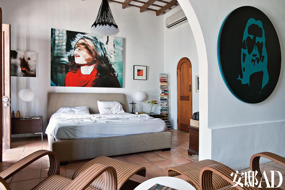 """主卧墙上挂有Judith Eisler的画作《Blondie》,两边分别是Karlo Ibarra和Matthew Higgs的作品。85 Lamps吊灯为Rody Graumans的设计,夜灯则出自George Nelson之手。Charles 床头柜为Citterio为B&B Italia所设计的产品。近景处,圆形画作来自Aaron Young,一对躺椅则由Jorge Pardo所设计。"""" 收集艺术品和人际交往有很大的关联,它是记录生命的一种形式,每一件艺术品都记录着我们的一段生活阅历。"""""""