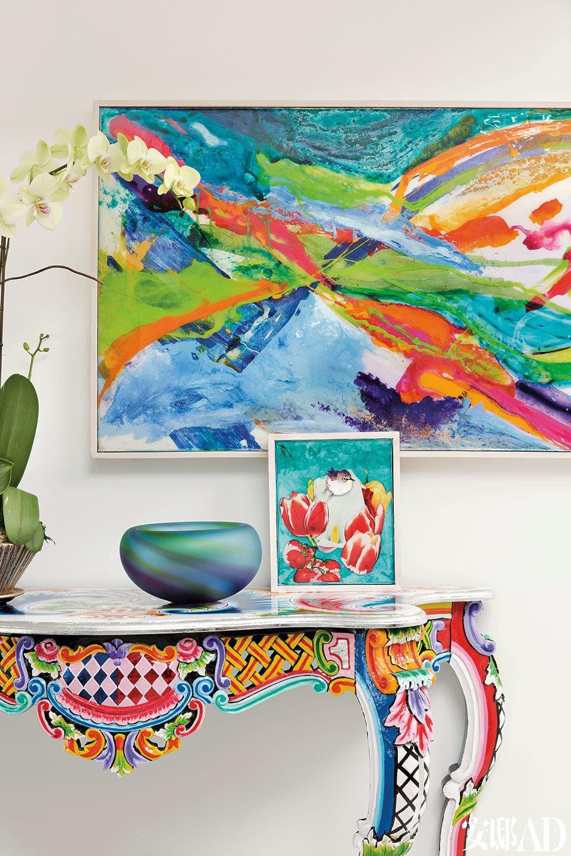 """七彩条案原产于德国,桌上的花卉小画和墙上悬挂的""""神秘之山(Mystic Mountain)""""都是女主人的作品。"""