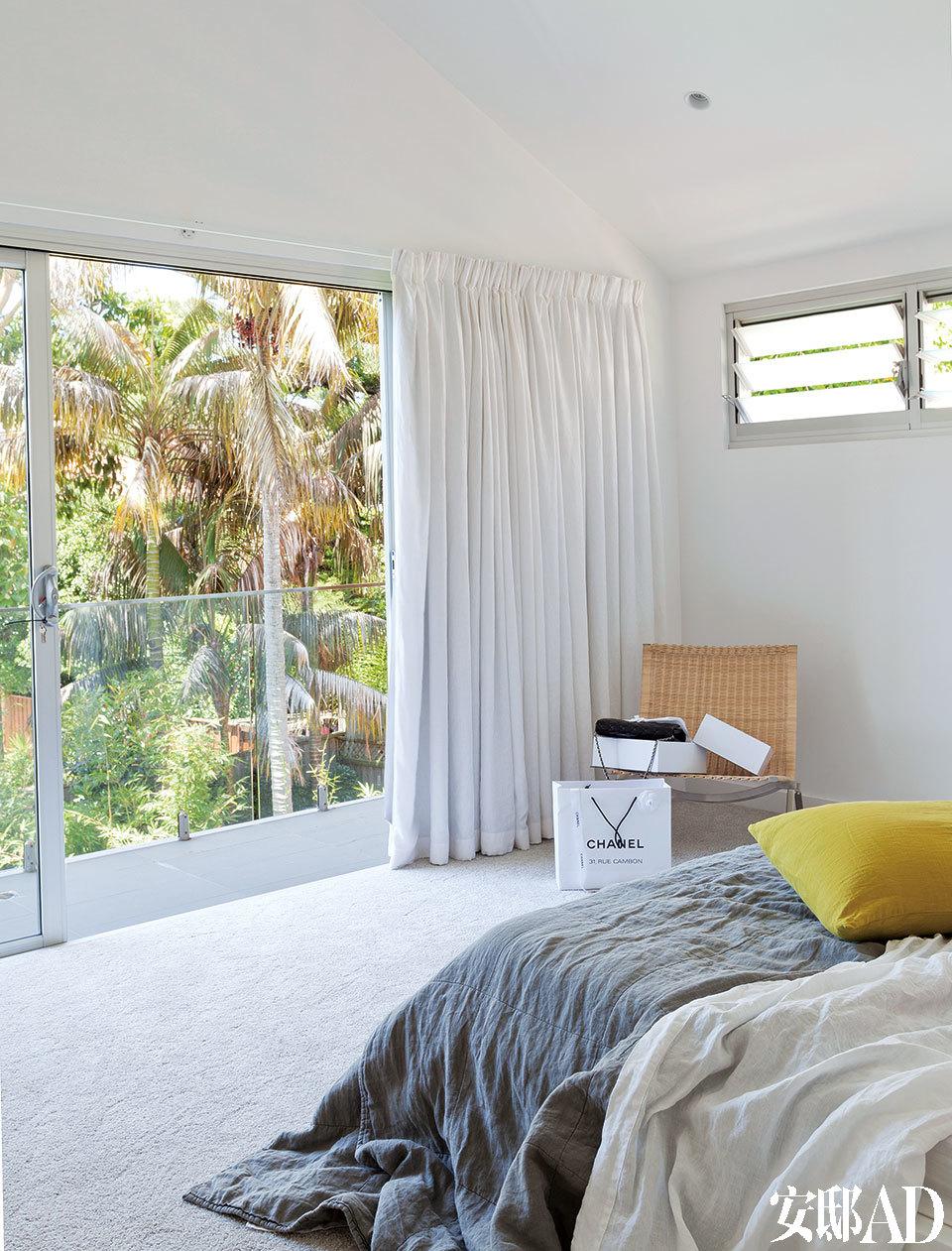 """宽大的卧室有推拉玻璃门直通户外,躺在床上就可以看尽花园美景。主卧位于二楼,藤编座椅来自PK22,窗帘是定制的白色亚麻窗帘,床上用品来自Ondene,柠檬黄靠垫购于巴黎梅西百货,地毯来自Harvey Norman,名为""""初雪""""。"""
