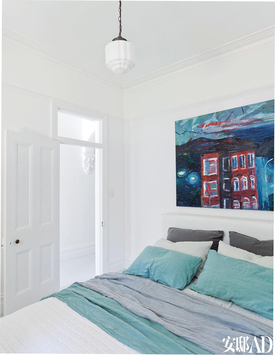 进门后的第一间卧室是主人用来招待自己众多国际宾客的客房。床上用品来自Ondene,床头的画作是当地画家所描绘的邦迪海滩。吊灯来自Chippendale Restorations。