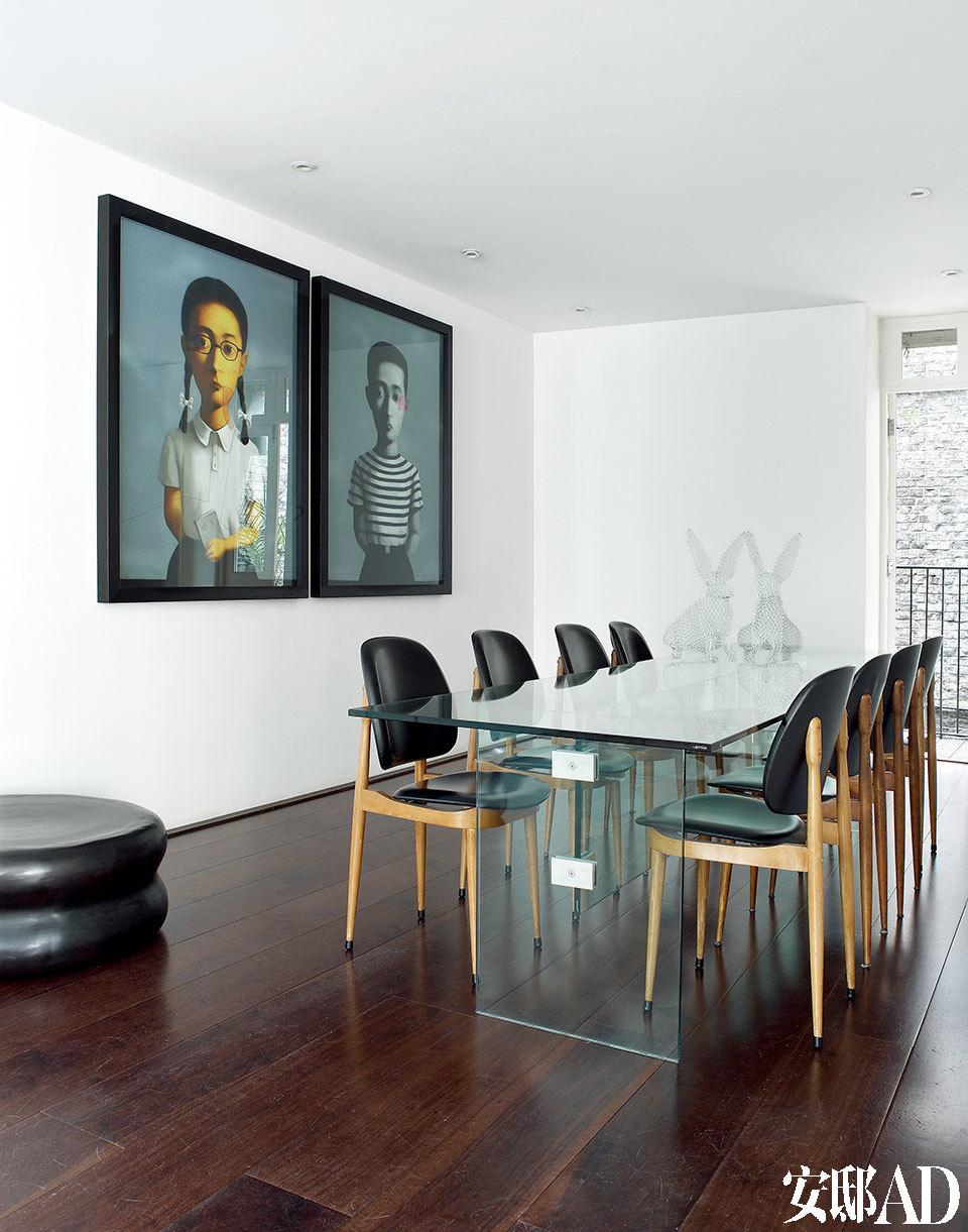 "John设计的玻璃餐桌上,摆着两只Benedetta Mori Ubaldini创作的金属丝雕塑白兔,餐椅来自20世纪50年代,购买于Albemarle大街上的Paul Smith的商店。墙上挂着中国艺术家张晓刚""Big Family""系列作品中的《男孩》和《女孩》。"
