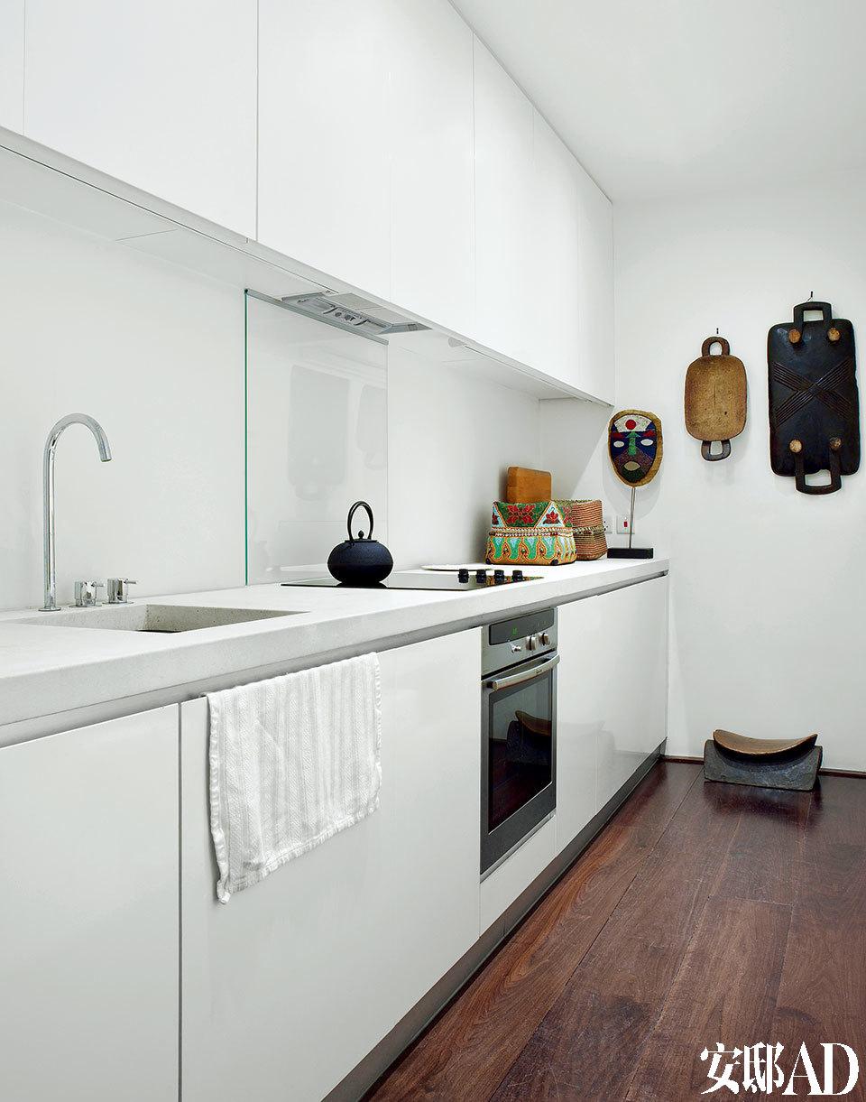 厨房里也大面积运用了石灰岩材质,非洲风格的面具购自诺丁山的TribalGathering London,手工木雕托盘则是主人肯尼亚之旅的收获。