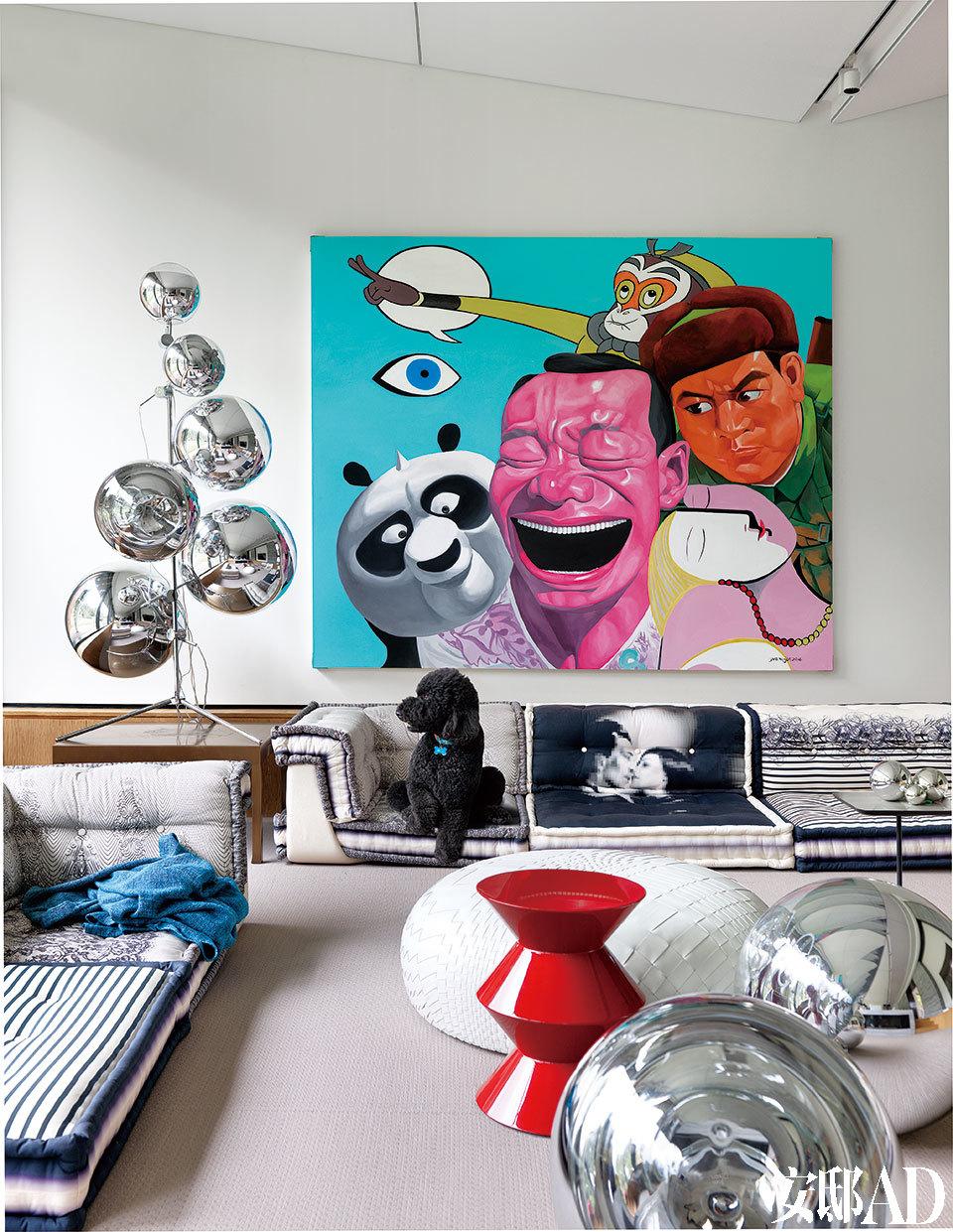 位于一层的另一个小客厅里,设计感十足的家具与艺术品成为主角。红色与橘色座椅来自B&B Italia,灰色沙发同样来自B&B Italia,名为Tufty-Too,白色落地灯来自Roll & Hill,架子上的枝形烛台来自Tom Dixon,以上物品均购于家天地。新建的大客厅空间是主人与客人们的最爱。王中磊说自己没事时,最爱坐在这里放空。墙上的艺术品是岳敏君为这个家定制的。画作旁的银色球形灯来自Tom Dixon,名为Mirror Balls Tree,白色矮墩是Dew by Nendo,来自Moroso,红色咖啡桌来自Minotti,银色球形墩来自Tom Dixon,同样属于Mirror Balls系列。以上物品均来自家天地。沙发为罗奇堡经典的麻将沙发,此图案系列为Jean Paul Gaultier的设计。沙发上的蓝色盖毯来自宜家家居。多年好友岳敏君特意为王中磊创作的大幅画作,被挂在客厅里最好的位置。画中特意加入了多个经典电影形象,还有男主人平生第一个崇拜的偶像————董存瑞!