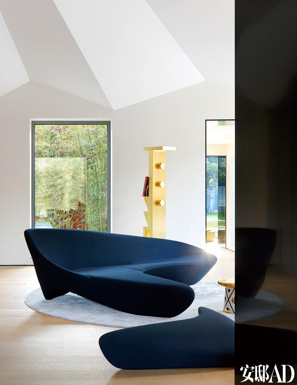 连接新建客厅空间和老建筑的走廊门厅里,建筑感十足的家具与窗外的中式意境庭院景致相混搭,十分精彩。沙发是建筑师Zaha Hadid为B&B Italia设计的MOON System系列。远处的书与衣帽两用架是Tom Dixon的Mass系列。二者均来自家天地。至于沙发旁的金色小凳则是Jaime Hayon为BOSA设计的系列,来自连卡佛。