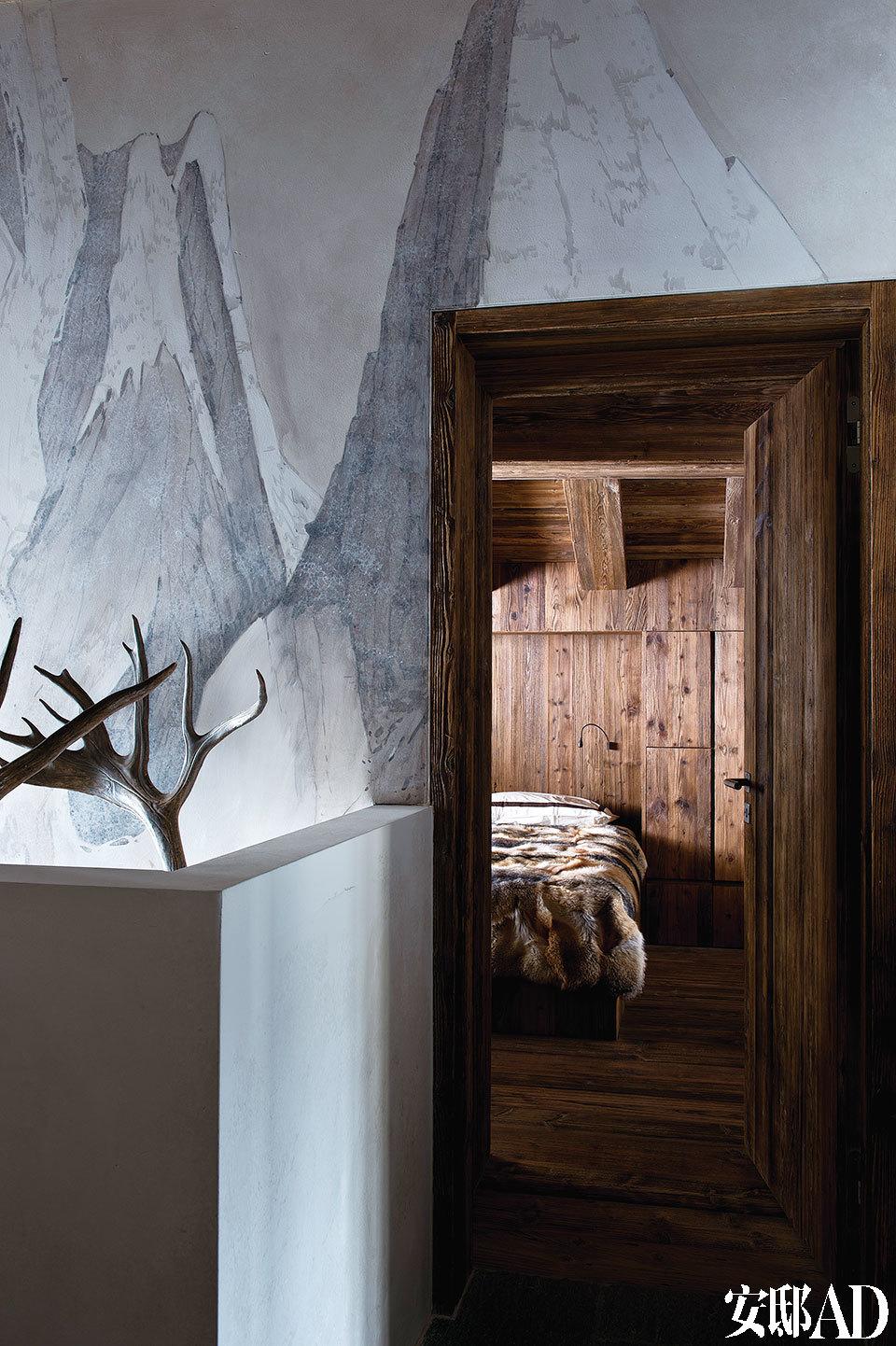 灰白色的墙壁,搭配卧室的木头质地,一截露出的鹿角衬着,最适合做一段山中美梦。