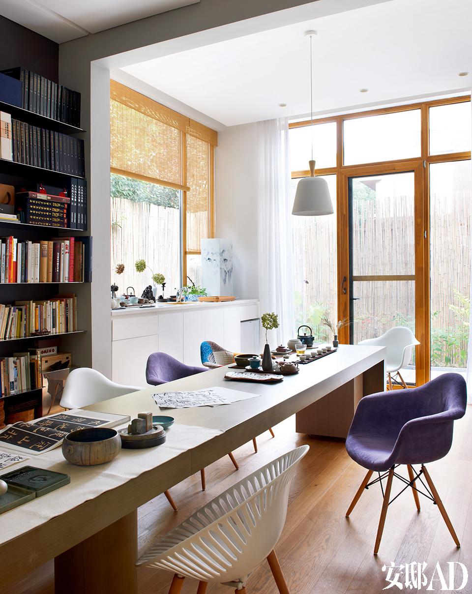 """渝儿的茶室,茶桌上摆着茶席和一束名为""""安娜贝尔""""的干绣球花,窗外就是她的竹篱和小花园。吊灯是北欧设计,购自德国,座椅均为Eames椅。"""